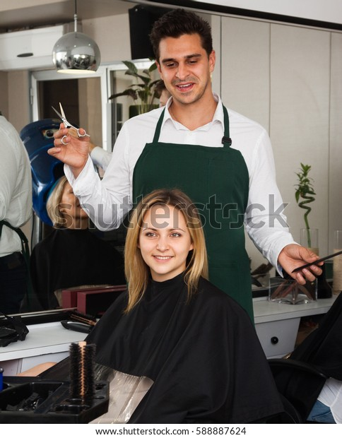 Professional hairdresser cuts hair of blonde girl at hairdressing saloon