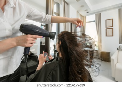Professional hairdresser drying client's hair with blow-dryer in beauty salon