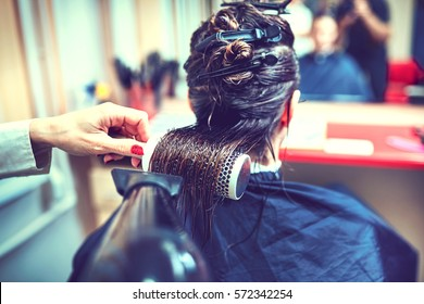 Professional hairdresser drying hair, in ctudio