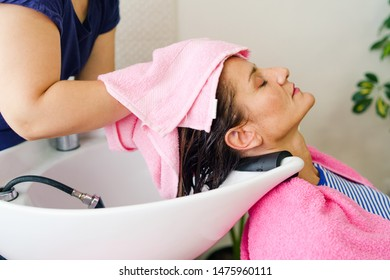 Professional hairdresser drying woman's hair after washing using towel at the hairdressing saloon salon