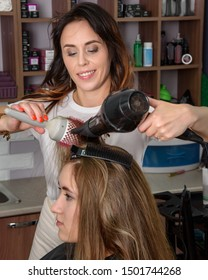 Professional hairdresser girl drying long hair hairdryer and comb. Process of hair styling in beauty salon