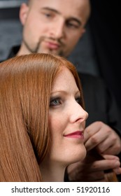 Professional hairdresser with long red hair fashion model at black luxury salon