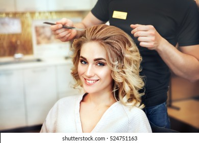 Professional hairdresser makes hairstyle for a long hair model