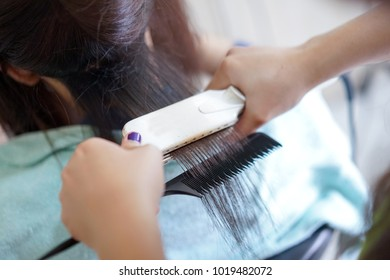 Professional hairdresser makes straight aligns the hair with hair iron to a young girl in a beauty salon.