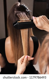 professional hairdresser making a gauffer hairdo of a woman with long hair in a beauty salon. concept of stylist training