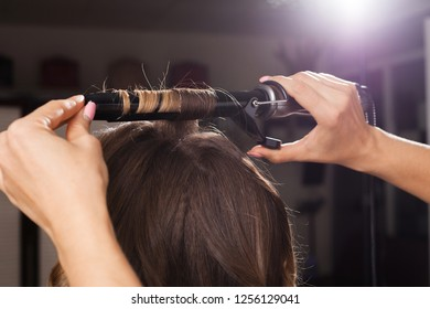 professional hairdresser making a hair curling to a client with long hair in a beauty salon. concept of stylist training