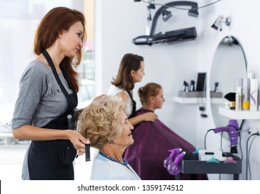Professional hairdresser making hairstyle for elderly female client in hair salon