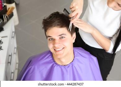 Professional hairdresser making stylish haircut