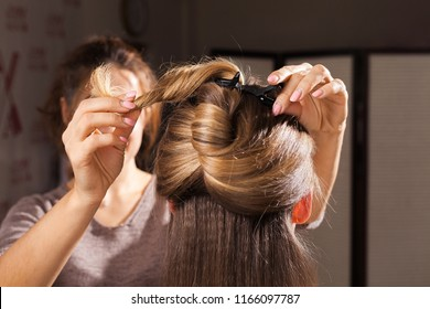 professional hairdresser making an unusual coiffure with a topknot to a brown haired young model in a beauty salon