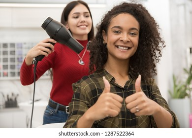 Professional hairdresser smiling and finishing stylish coiffure using hair dryer. Beautiful brunette girl happy after visiting luxury beauty salon. Satisfied client showing like after making haircut.