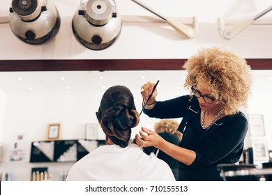 Professional hairdresser styling the hair of a customer at salon. Female hair stylist setting hair in fashionable design.