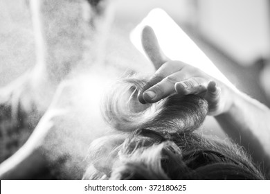 Professional hairdresser styling with hairspray long woman curly hair. Emotional detail of the hands making hot styling at hair salon. Black and white photography. Blurred background. Unusual view.