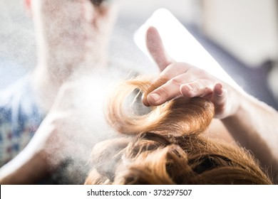 Professional hairdresser styling with hairspray long woman curly hair. Emotional detail of the hands making hot styling at hair salon. Color toned image. Blurred background.