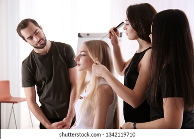 Professional hairdresser and trainees working with client in salon. Apprenticeship concept