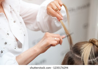 Professional hairdresser in a white coat brushes a curl of female hair in a beauty salon making a hairdo
