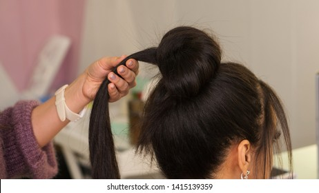 Professional hairdresser working with client in salon. Earlock hair in hairstylist's hand Master class to create upper bun hairstyle. Tutorial, advanced course. Apprenticeship concept.