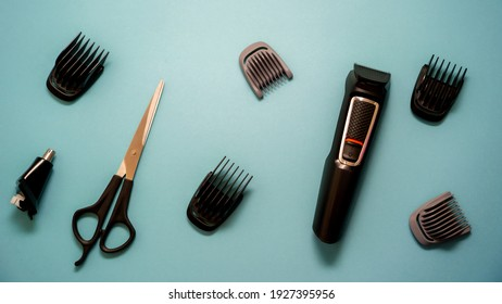 Professional hairdressing tools, hair clipper with attachments and scissors on a blue background
