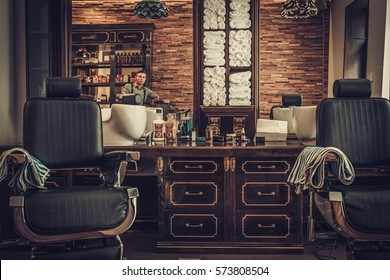 Professional hairstylist in barbershop interior