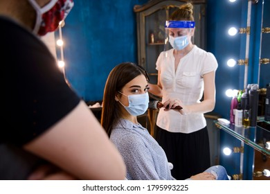 Professional hairstylists with masks on their faces, doing a hair job on a woman in a beauty salon during COVID-19 pandemic.