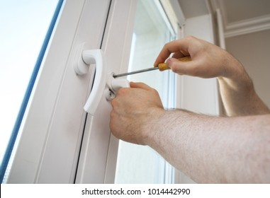 Professional handyman fixing window handle at home.