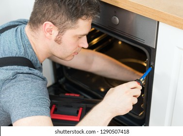Professional handyman in overalls repairing domestic oven in the kitchen.