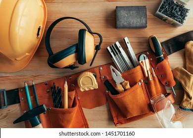 Professional handyman tool belt on the desk in workshop