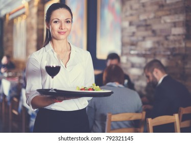 Professional happy  waitress holding serving tray for restaurant guests
