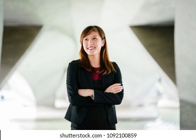 Professional head shot (portrait) of a young, attractive Chinese Asian woman smiling as she crosses her arms under a bridge in Asia.