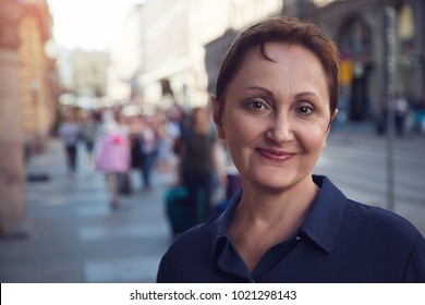 Professional headshot of a middle aged woman walking in city. Outdoor portrait of a middle aged female. Urban background. Street style shot. Filtered.