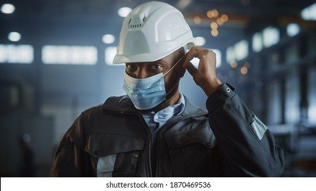 Professional Heavy Industry Engineer Worker is Putting On Safety Face Mask in a Steel Factory. Black African American Industrial Specialist in Hard Hat Standing in a Metal Construction Manufacture.