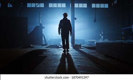 Professional Heavy Industry Engineer Worker Wearing Uniform, Flashlight on the Hard Hat in a Steel Factory. Industrial Specialist Walking Towards the Camera in a Dark Metal Construction Manufacture.