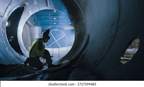 Professional Heavy Industry Welder Working Inside Pipe, Wears Helmet and Starts Welding. Construction of the Oil, Natural Gas and Fuels Transport Pipeline. Industrial Manufacturing Factory.
