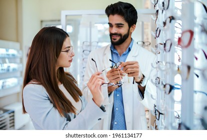 Professional help and advice. Woman in optic store choosing a new eyeglasses frame. Medical, health care concept