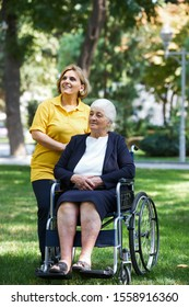 Professional helpful caregiver and handicapped senior woman. Daughter cares for mother. Health visitor and a senior woman during visit. Careful caregiver taking care of the patient, outdoors.