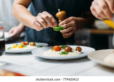 Professional high end chef or cook seasons and decorates parmesan risotto with freshly grounded black pepper and fresh leaves of basil. Home cooking or restaurant preparation