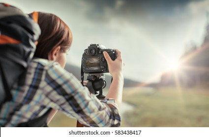 Professional hiker and photographer shooting in nature with a digital camera and a tripod, back view