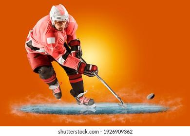 Professional hockey player skating on ice. Isolated on orange