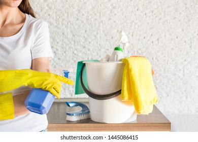 professional home cleaning. A young woman cleans the apartment. Close-up, rags, sponges and bucket, supplies staff.