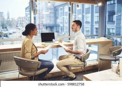 Professional human resources manager conducting interview with confident male candidate for vacancy reading interview while asking question from application sitting in coworking space during meeting