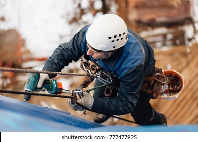 Professional industrial climber in helmet and uniform works at height. Risky extreme job. Industrial climbing at construction site