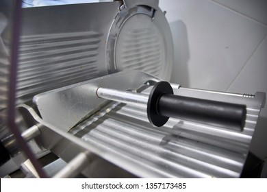Professional industrial restaurant meat slicer for layered pieces of ham.