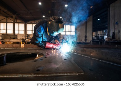 Professional industrial welder welding metal parts in metalworking factory. Worker wearing protective mask and gloves. Flash and sparks flying.