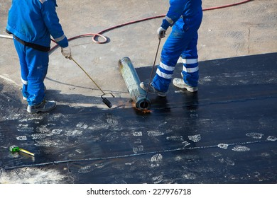 Professional installation of waterproofing on the concrete foundation. Two worker at construction site.