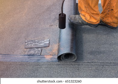 Professional installation of waterproofing on the concrete foundation. Roofer installing Roofing felt with heating and melting of bitumen roll by torch on flame during roof repair. Copy space