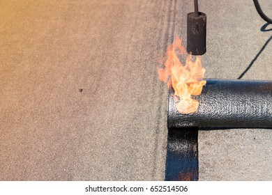 Professional installation of waterproofing on the concrete foundation. Roofer installing Roofing felt with heating and melting of bitumen roll by torch on flame during roof repair Copy space