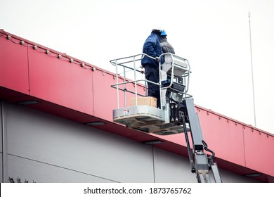 Professional installation work on a construction building site. Assemblers perform high-altitude installation works on the lifts platforms. - Shutterstock ID 1873765762