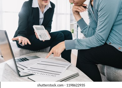 professional insurance agent showing the amount of the insurance case product to the shrewd housewife in the living room. businesswoman holding calculator and introducing the new project.