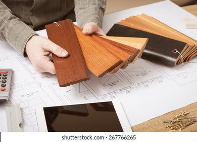 Professional interior designer holding wood swatches for baseboard and skirting, hands close up with desktop on background