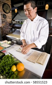 Professional Japanese chef in restaurant making sushi rolls
