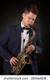 Professional jazz musician playing saxophone. Young man in suit performing classical symphony.